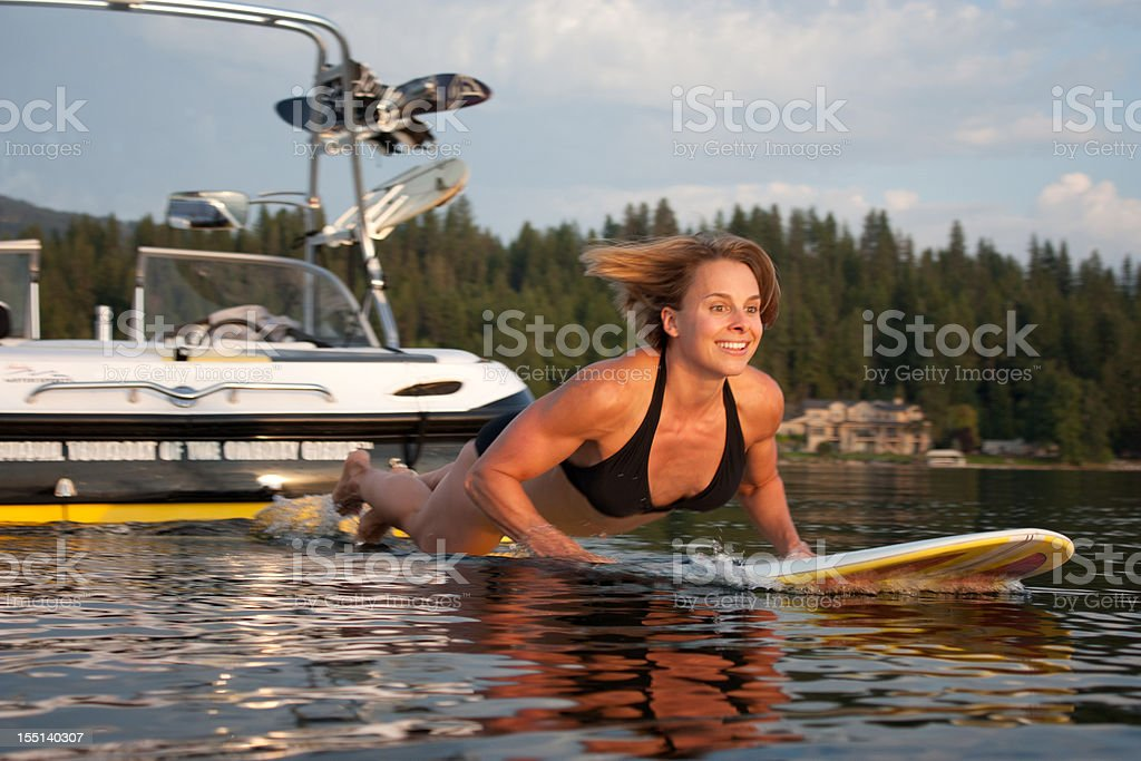Girl jumping onto surfboard from back of boat royalty-free stock photo