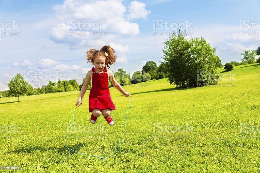 Girl jumping over the rope stock photo