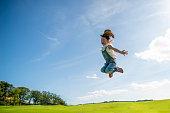 青い空にジャンプの女の子