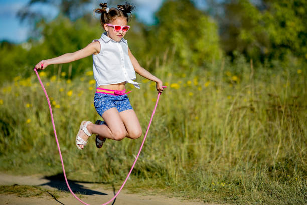 girl jumping with a rope stock photo