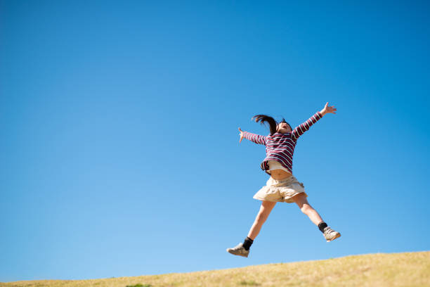 Girl jumping with open arms stock photo
