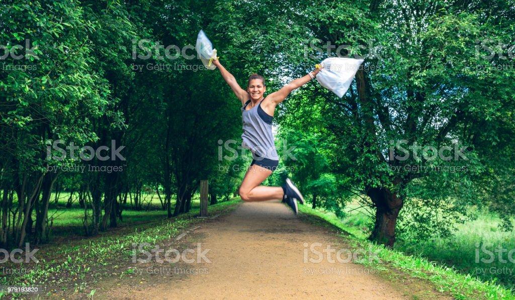 Mädchen mit Müllbeutel nach Plogging springen - Lizenzfrei Aktiver Lebensstil Stock-Foto