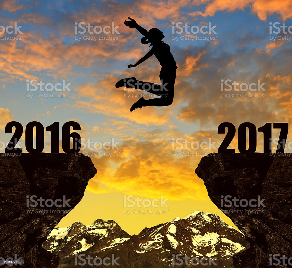Girl jumps across the gap to the New Year 2017 stock photo