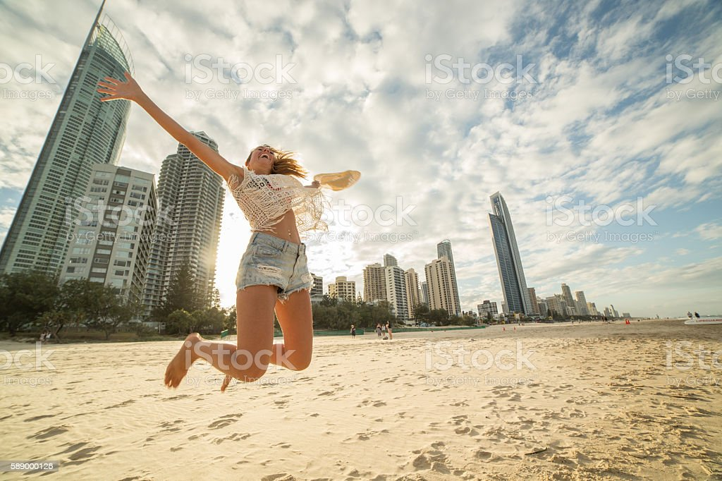 Girl jumps on beach high up in air at sunset stock photo