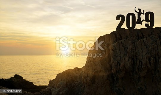 Silhouette of a girl jumps up while celebrating New Year 2019.