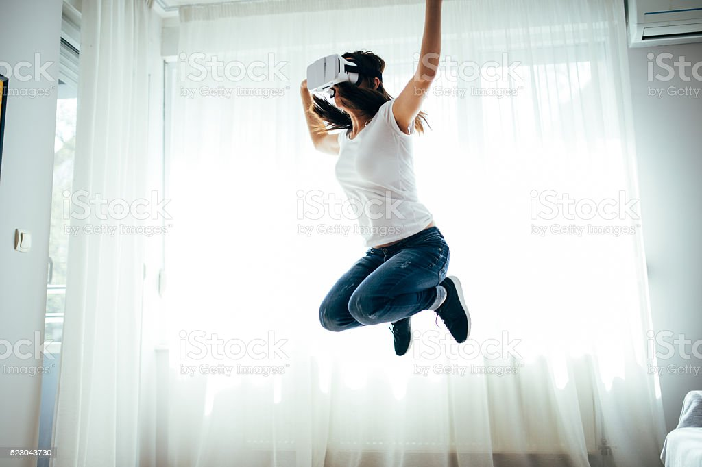 Girl jumps with VR headset stock photo