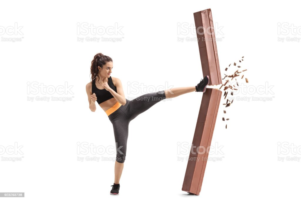 Girl kicking and breaking a chocolate bar stock photo