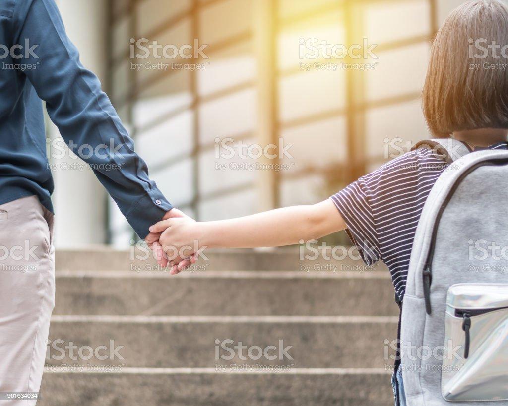 Chica chico (estudiante de primaria) llevar mochilas subiendo la escalera del edificio educativo va a clase para la parte posterior de la mano de padre madre a primer día de la escuela y traer niños para trabajar el concepto - foto de stock