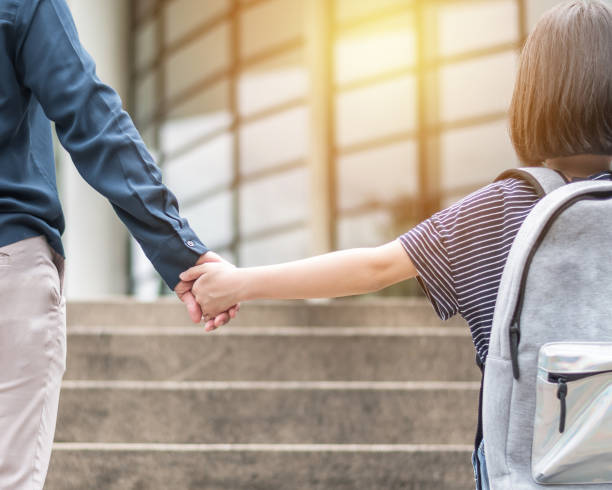 girl kid (elementary student) carrying backpacks holding parent mother's hand walking up educational building's stair going to class for back to school first day and bring kid to work concept - teachers day stock photos and pictures