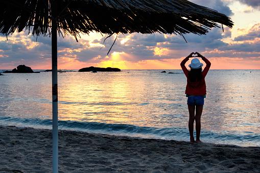 Girl kid holding a heart shape for the ocean / sea. Love Concept.