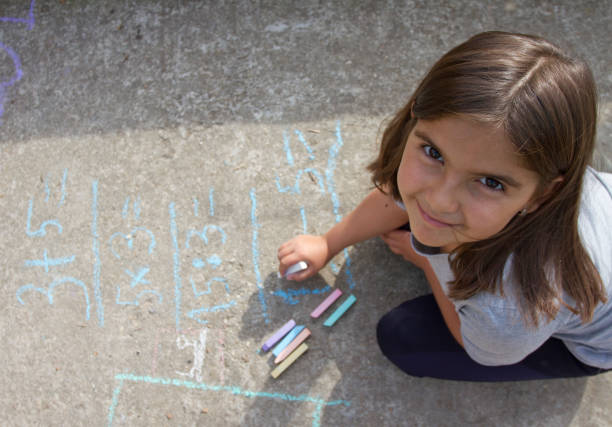 Girl kid thinking, writing and counting on mathematical equations with colored chalks on a pavement. School and vacation concept. Education concept. stock photo