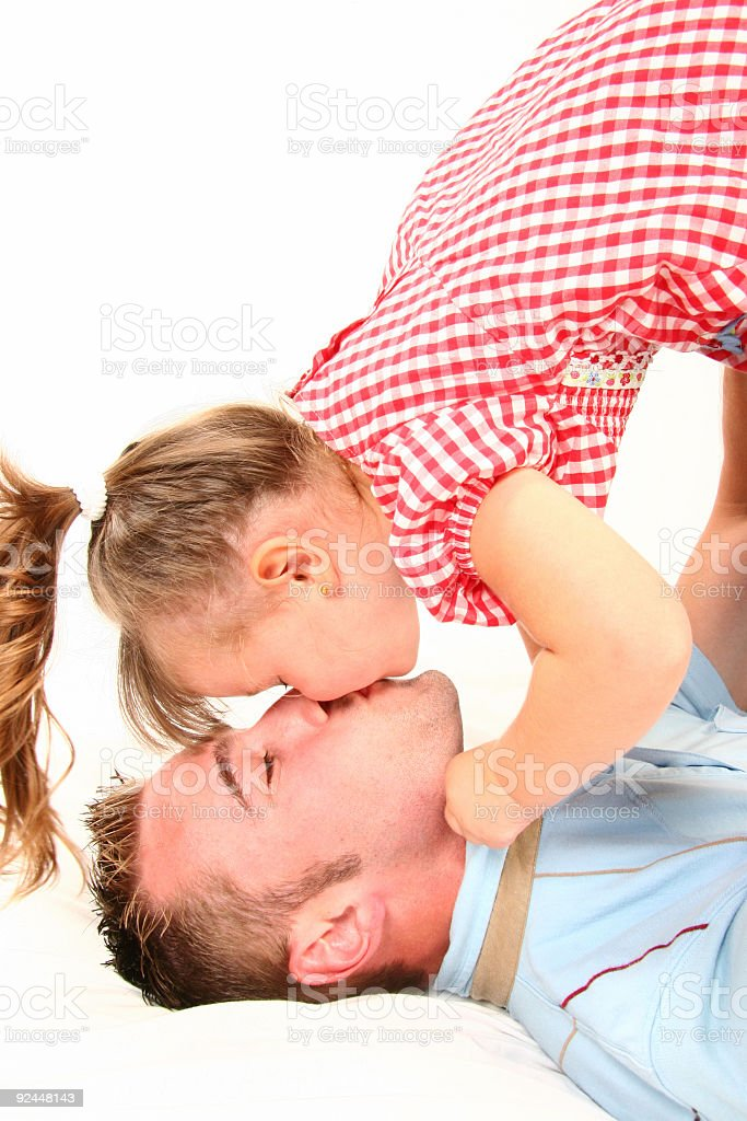girl kissing father stock photo