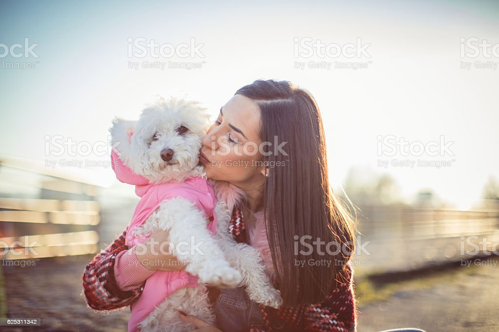 Girl kissing her dog poodle stock photo