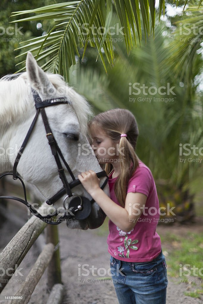 Girl kissing horse in yard stock photo