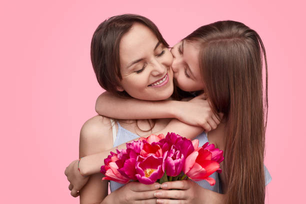 Girl kissing mother with spring bouquet stock photo