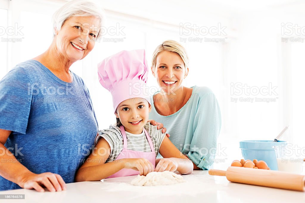 Girl Kneading Dough By Mother And Grandmother At Counter royalty-free stock photo