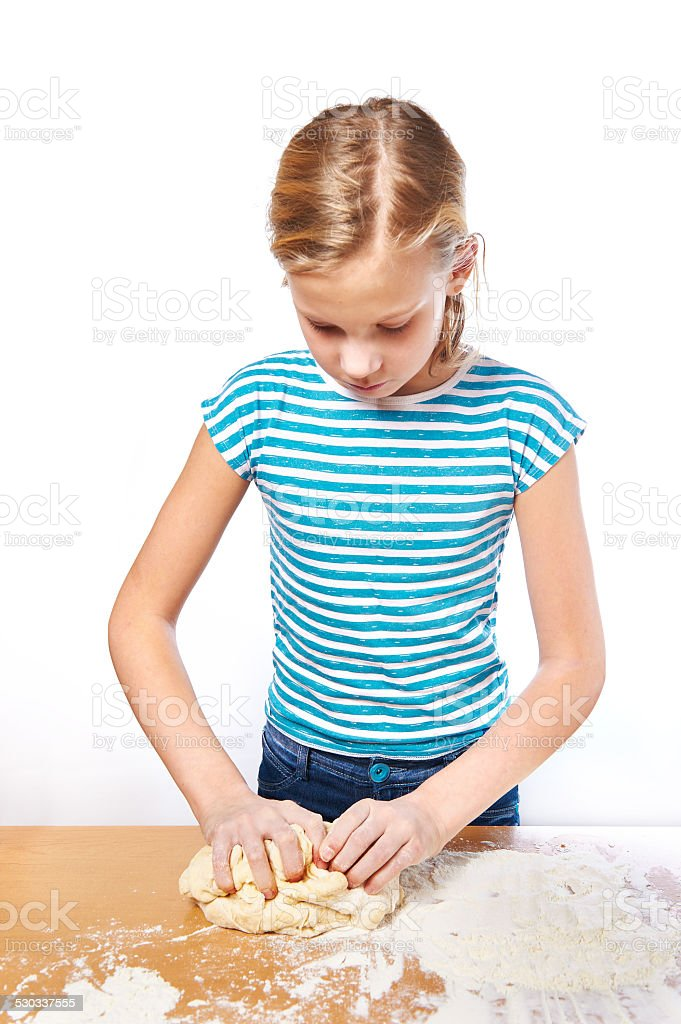 Girl kneads dough for pie on kitchen table isolated stock photo