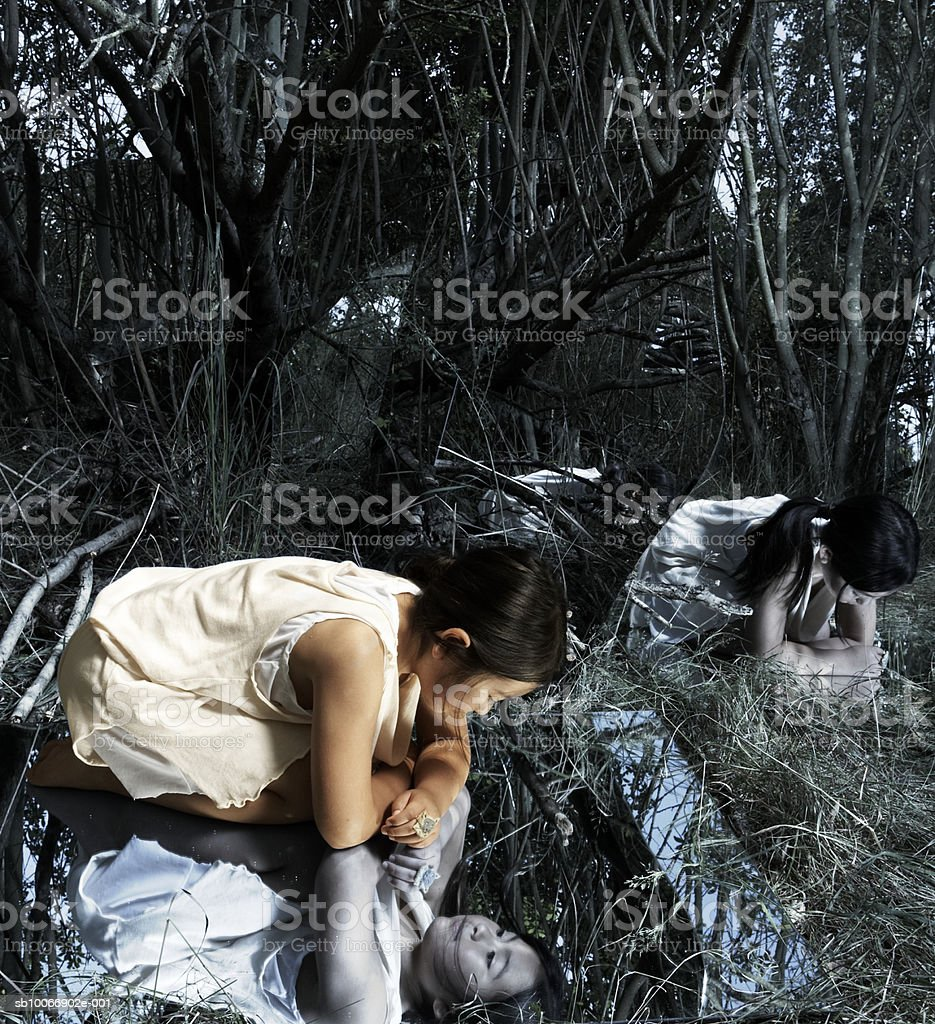 Girl (8-9) kneeling in grove, reflected in mirrors, (Digital Composite) royalty-free stock photo