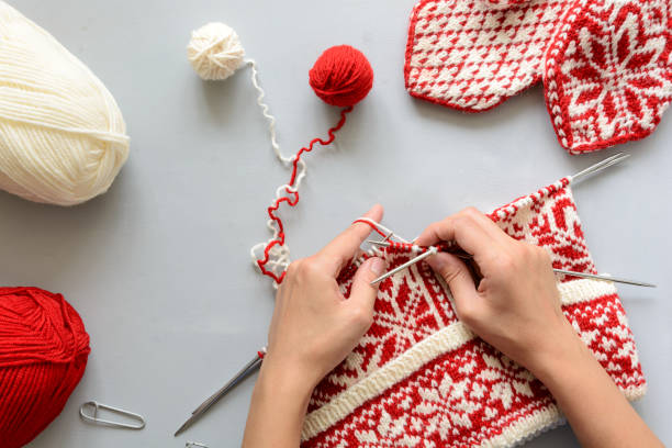 girl knits red and white norwegian jacquard hat knitting needles on gray wooden background. process of knitting. top view. flat lay - lavorare a maglia foto e immagini stock