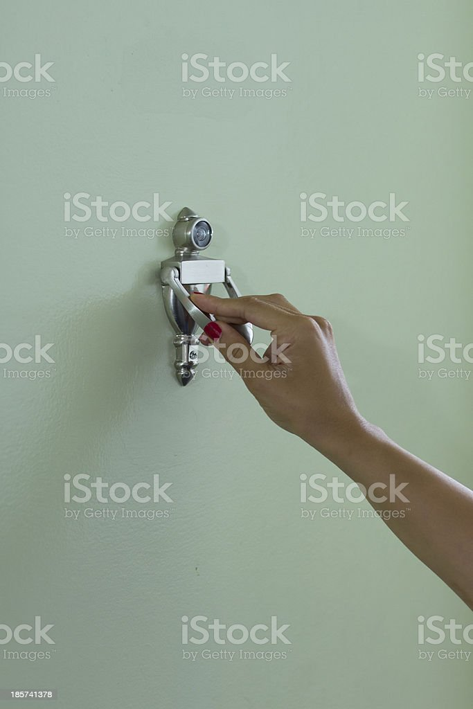 Girl knocking on green door stock photo