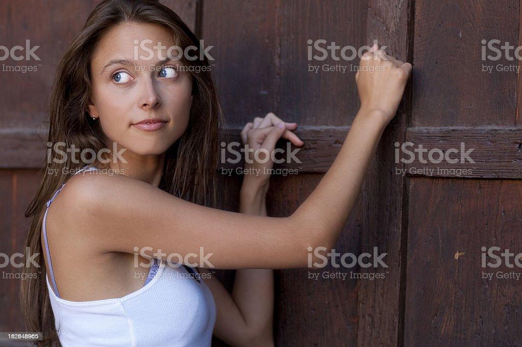 Girl Knocking Wooden Door stock photo