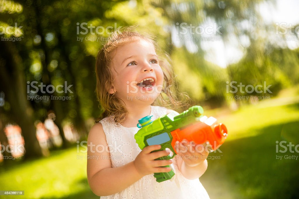 Girl laughing while splashing with squirt gun stock photo