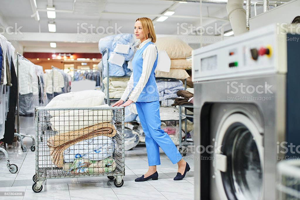 Girl Laundry worker rolls a cart with clean things – Foto