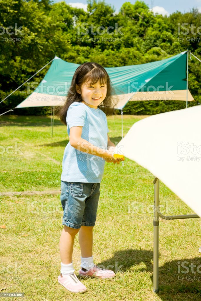 Girl lay a tablecloth at the campsite royalty-free stock photo