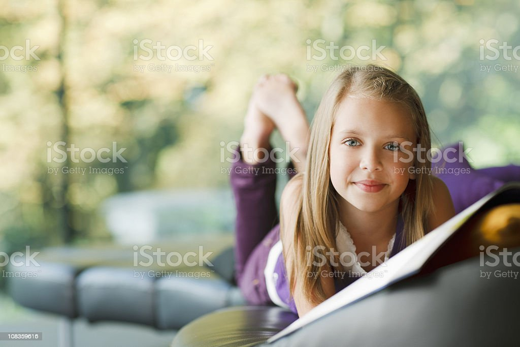 Girl laying down and reading book stock photo