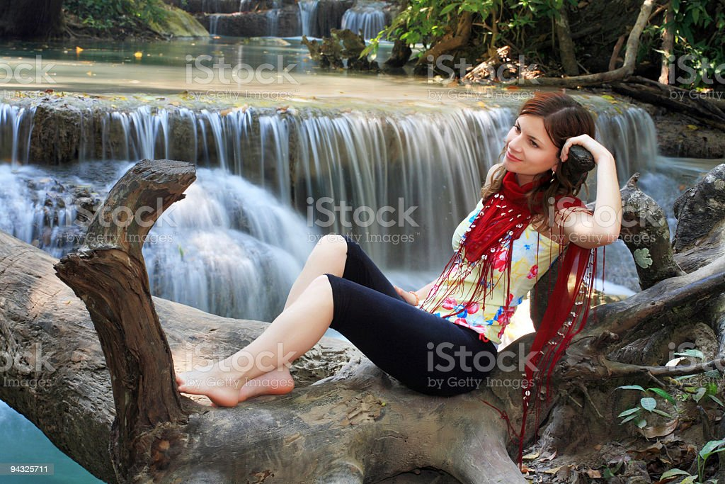 Girl laying down in tree against waterfalls royalty-free stock photo