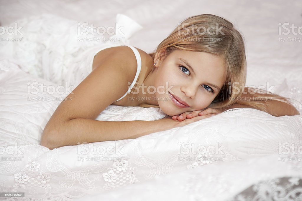 girl laying down on a bed stock photo more pictures of 12 13 years istock. Black Bedroom Furniture Sets. Home Design Ideas