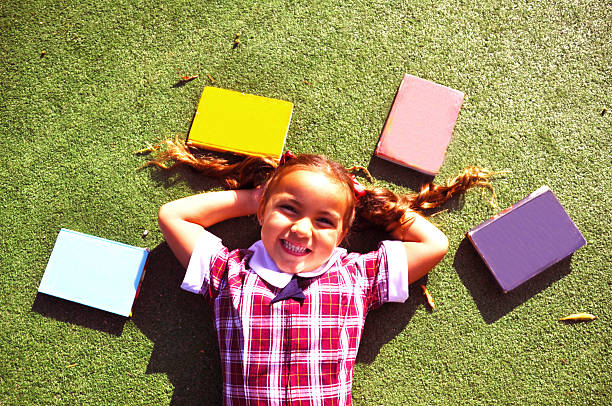 Girl laying down with books stock photo