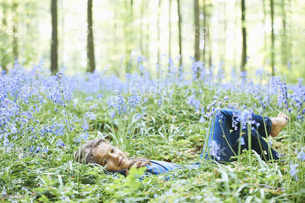 Girl laying in field of flowers stock photo