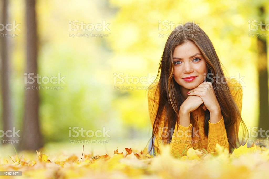 Girl laying on autumn leafs stock photo