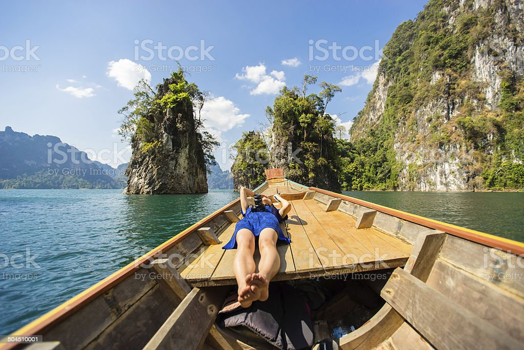 Girl laying on boat in Cheow Lan lake, Thailand stock photo