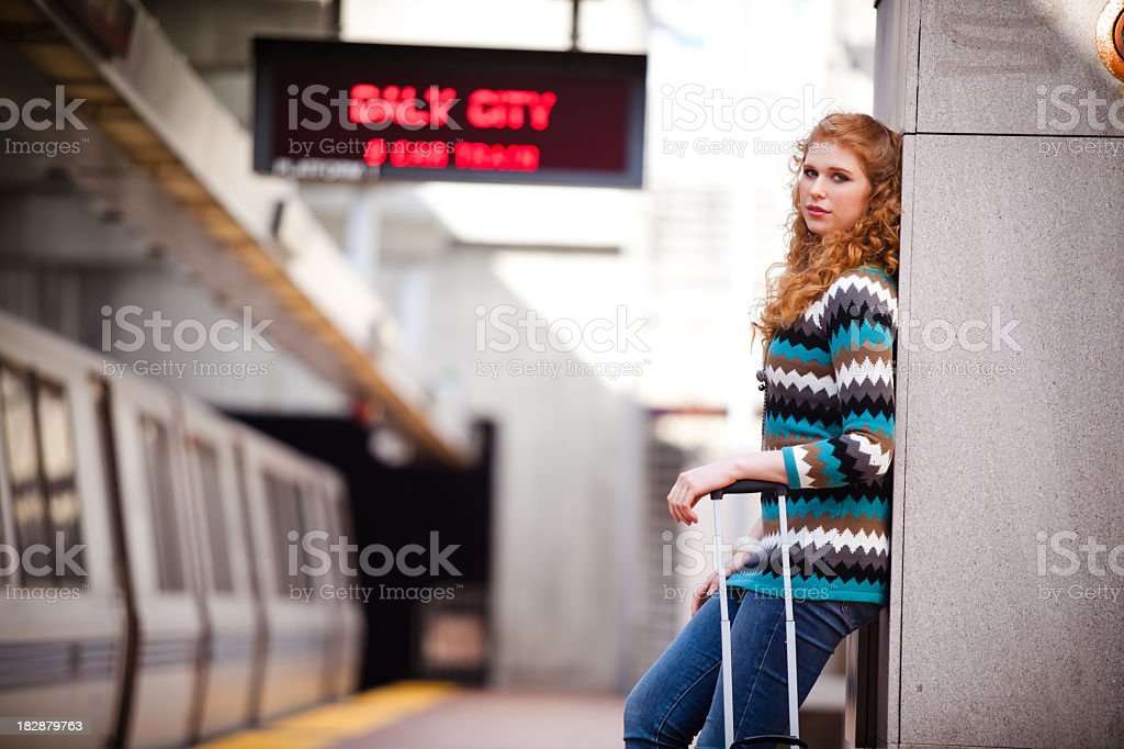 Girl leaning against wall at a BART station stock photo