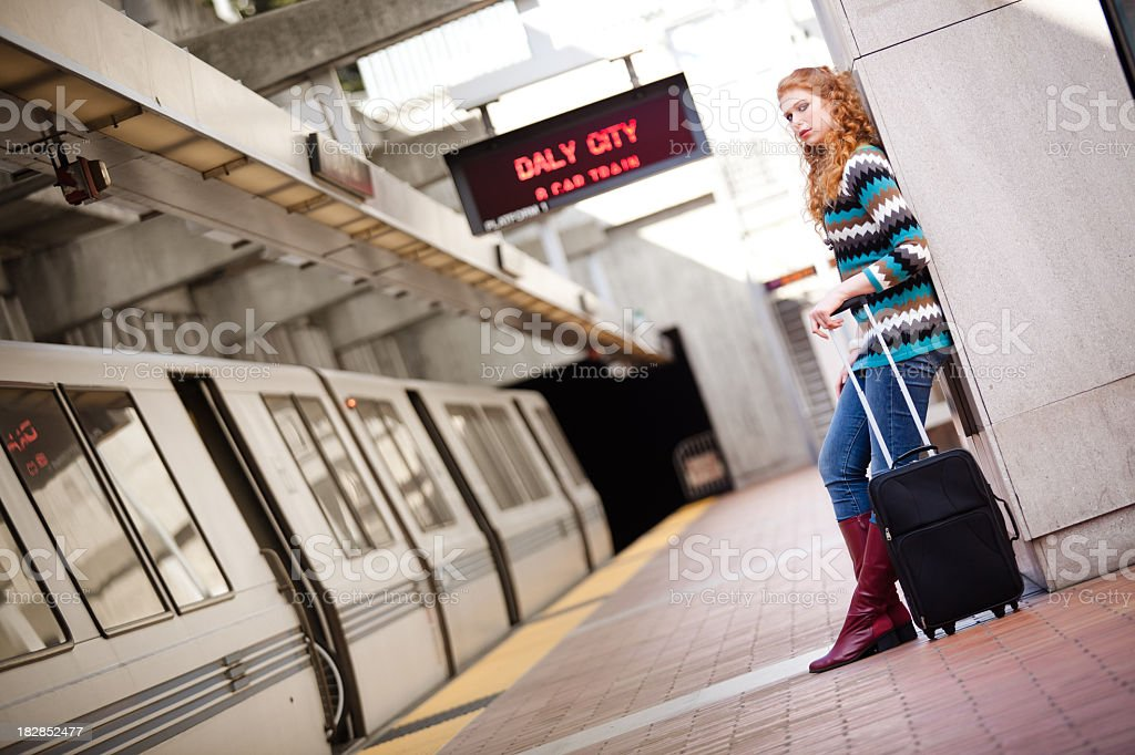 Girl leaning against wall at BART station stock photo