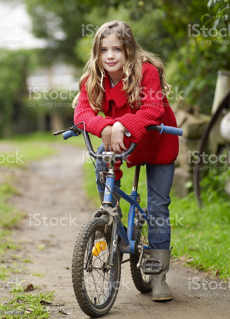 Girl leaning forward on her bicycle handlebars royalty-free stock photo