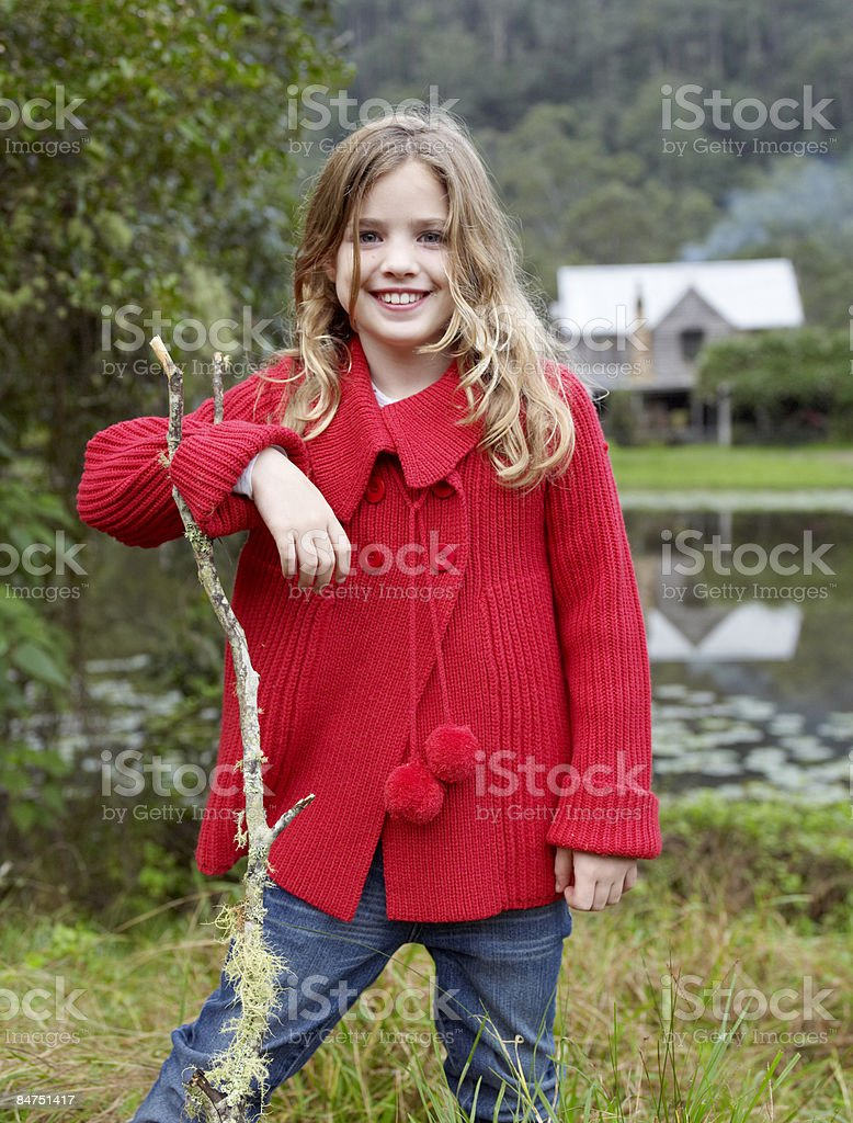 Girl leaning on a stick outdoors royalty-free stock photo