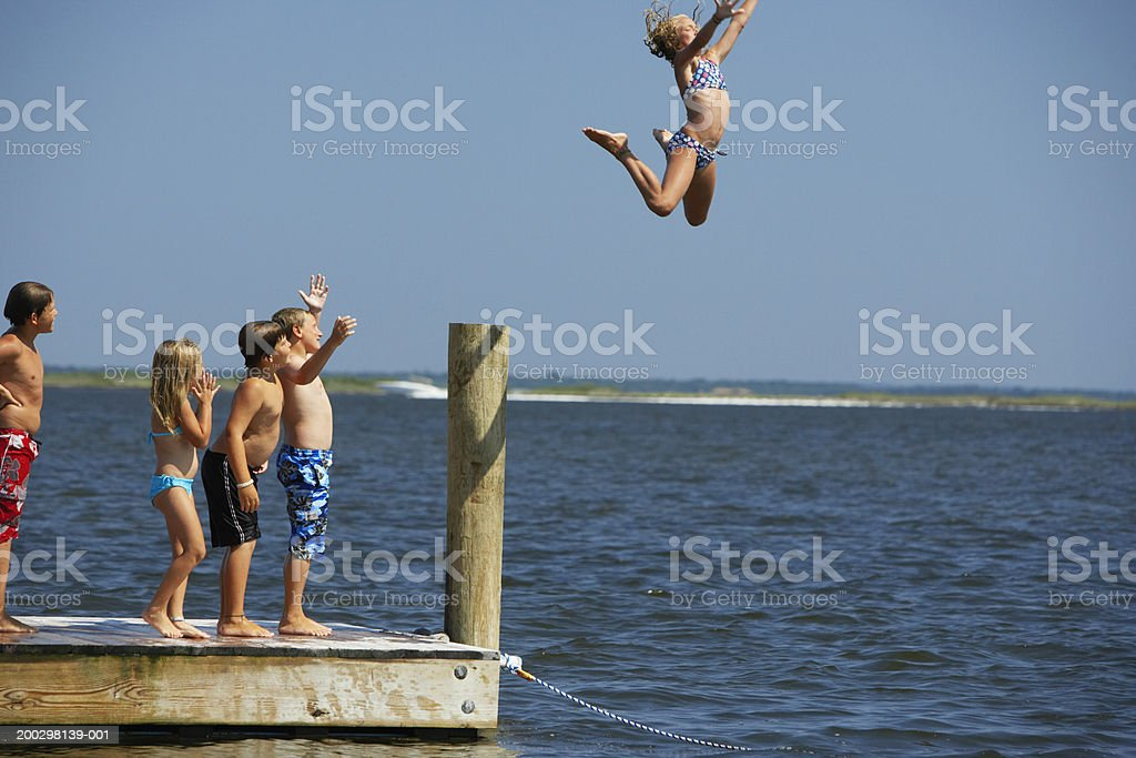 Girl (10-12) leaping off jetty, friends watching stock photo
