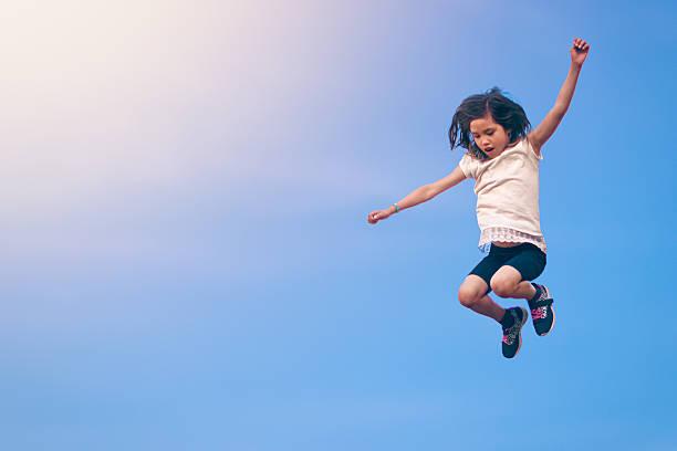 girl leaping towards the sky - trampolín artículos deportivos fotografías e imágenes de stock