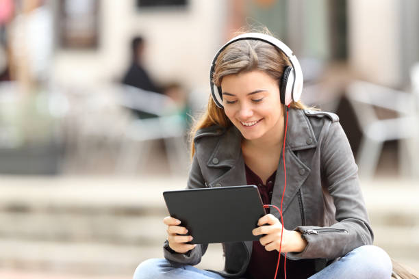 Girl learning on line with a tablet and headphones stock photo