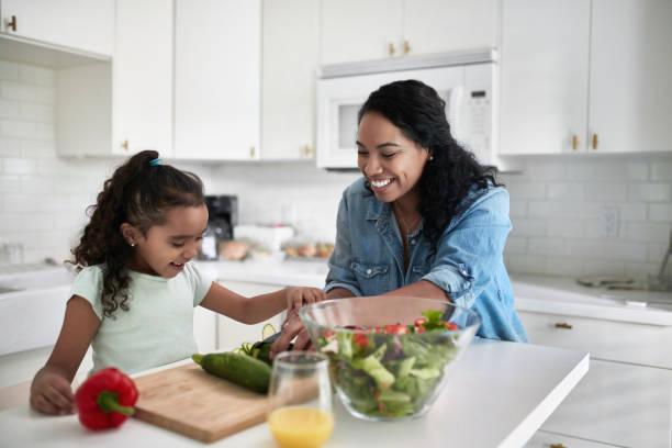 Mädchen lernen, Zucchini schneiden Sie von der Mutter – Foto