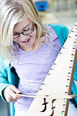 Little girl in music class, learning to play an instrument called a Bowed Psaltery.