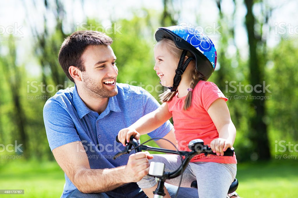 Girl learning to ride a bicycle with father stock photo