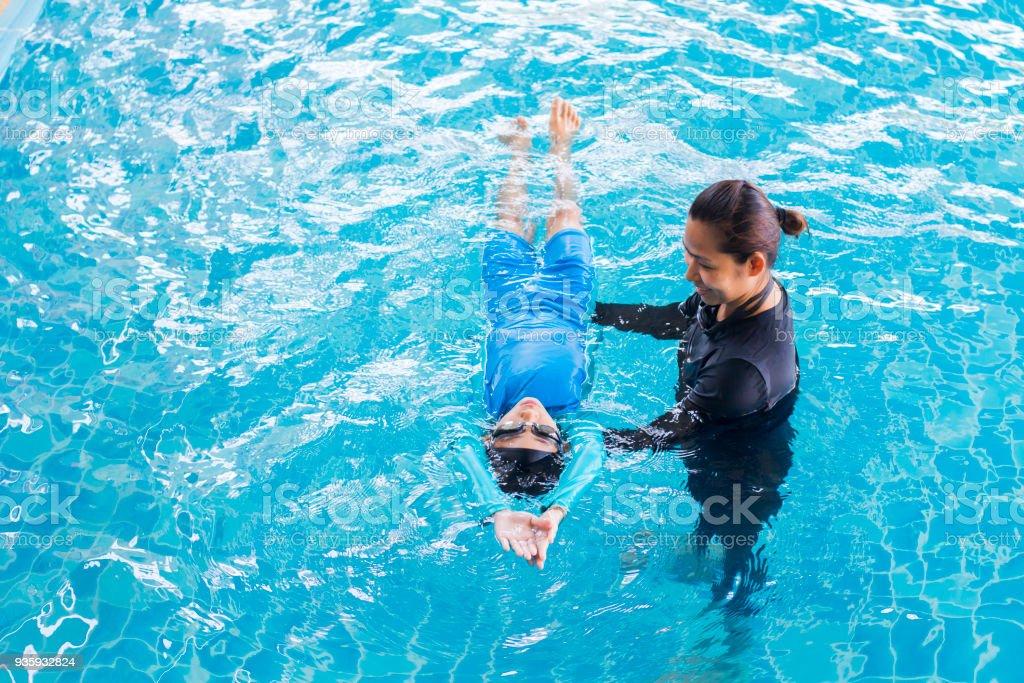 Menina aprendendo a nadar com o treinador no centro de lazer - foto de acervo