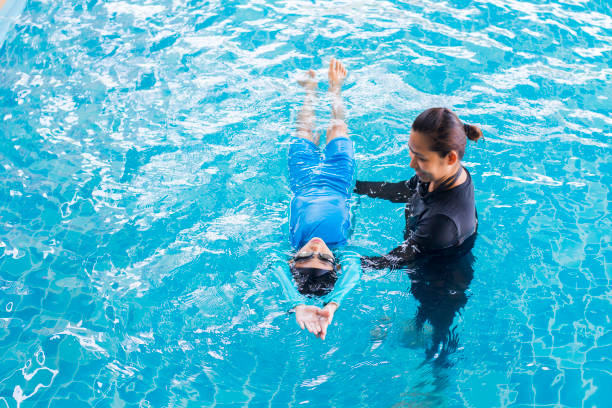 girl learning to swim with coach at the leisure center - swimming stock pictures, royalty-free photos & images