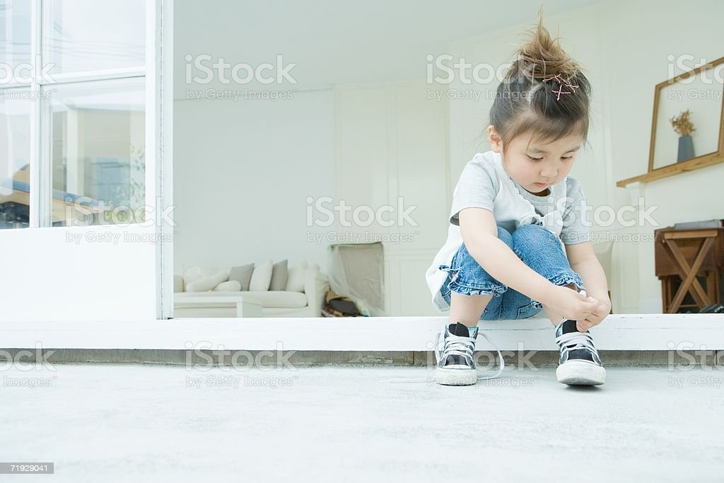 Girl learning to tie her shoelaces stock photo