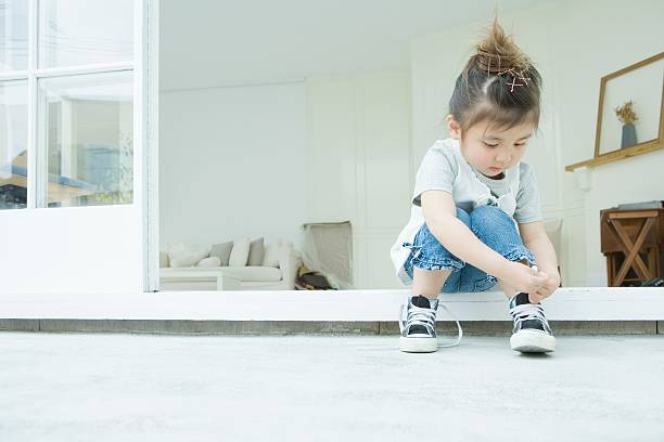 girl learning to tie her shoelaces - independence stock photos and pictures