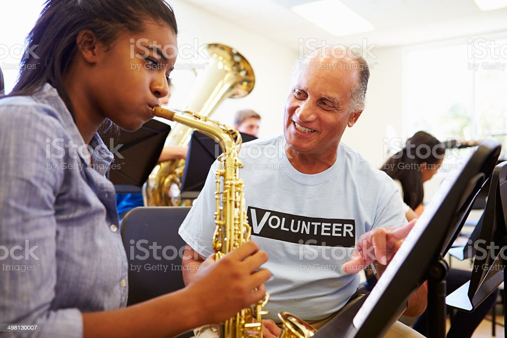 Girl learns saxophone in high school orchestra stock photo